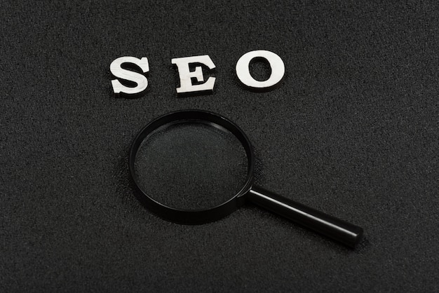 Search word or seo concept and magnifying glass on black background. close up