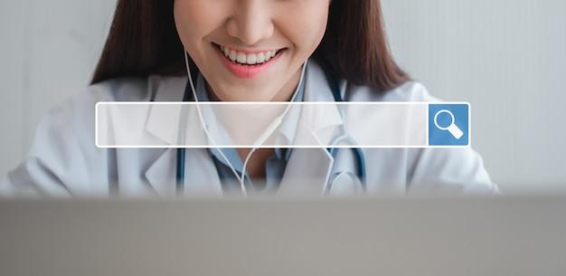 バックグラウンドでブラウジングインターネットバーを検索しているのは、アジアのセラピスト医師がインターネット上の患者とオンラインで訪問していることです。ブラウジングインターネットデータ情報ネットワーキングの概念を検索する