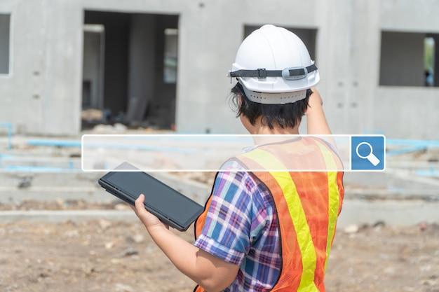 背景を閲覧しているインターネットバーを検索しているのは、白いヘルメットをかぶってタブレットを持っているエンジニアリングの女性です。ブラウジングインターネットデータ情報ネットワーキングの概念を検索する