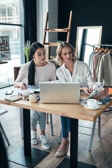 Ищем свежие идеи. красивые молодые женщины работают вместе и улыбаются