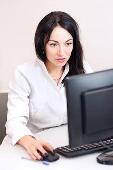 情報を検索しています。思慮深く見えるコンピューターで作業している白いローブの暗い髪の医者