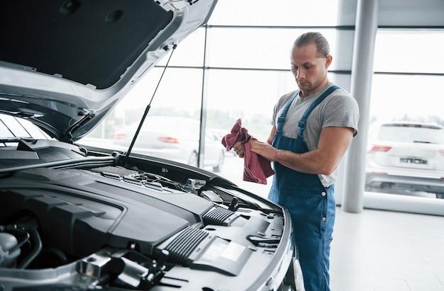 問題を探しています。青い制服を着た男は、壊れた車で働いています。修理を行っています。