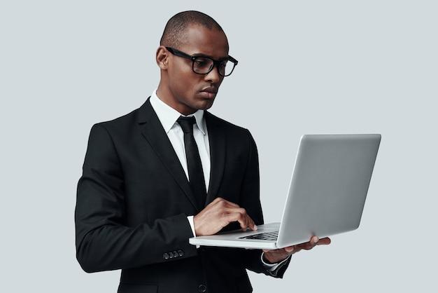 솔루션을 찾고 있습니다. 회색 배경에 서 있는 동안 컴퓨터를 사용하여 작업하는 formalwear에서 젊은 아프리카 남자