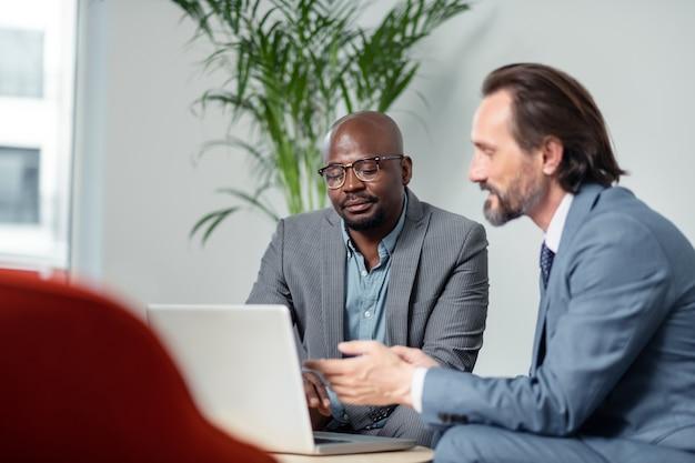 정보를 검색합니다. 프로젝트 정보를 검색하는 동안 노트북을 사용하는 두 명의 번영하는 비즈니스 파트너