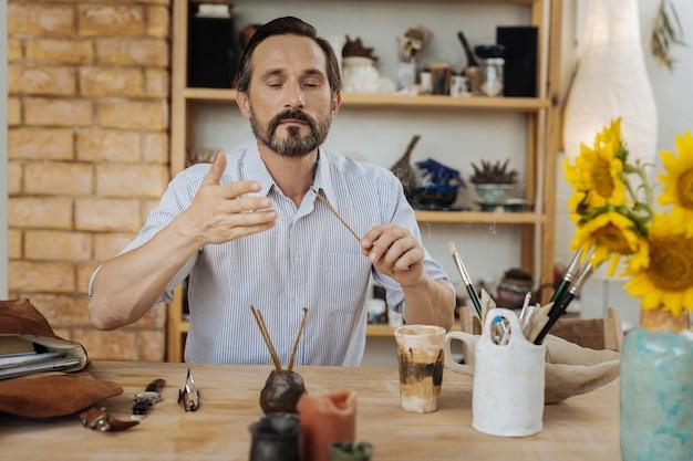 インスピレーションを求めています。彼のワークショップでアロマスティックを燃やしながらインスピレーションを探している黒髪の創造的な男