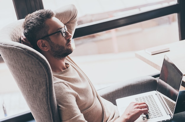 Searching for inspiration. side view of handsome man using his laptop and looking pensive while sitting in chair in front of window