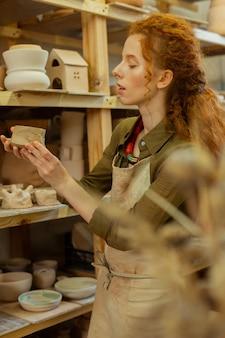 Ищем интересные штуки. внимательная рыжая девушка наслаждается различными глиняными фигурками и горшками во время посещения профессиональной мастерской