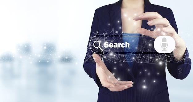 인터넷 데이터 검색. 웹 브라우징 개념입니다. 밝은 배경이 있는 가상 홀로그램 검색 데이터 아이콘을 들고 있는 두 손. 음성 명령이 있는 최소한의 빈 검색 표시줄.