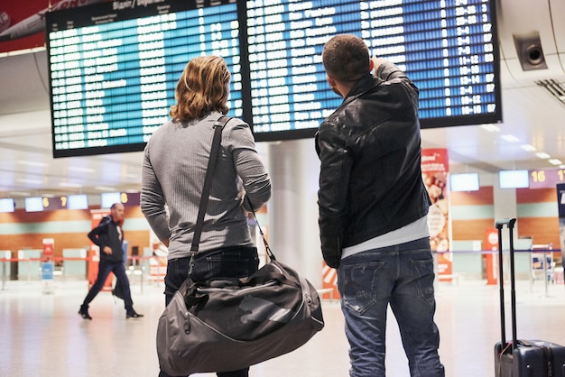 Searching their plane and when it arrives. photo of two comrades situating in airport near flight information display system