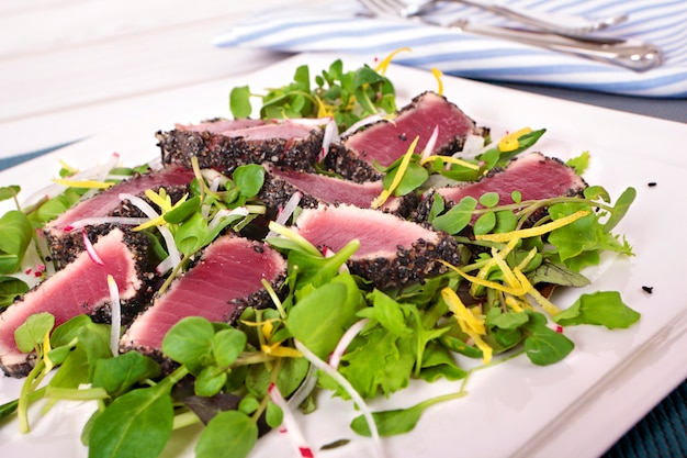 Запеченный тунец с зеленым салатом на столе
