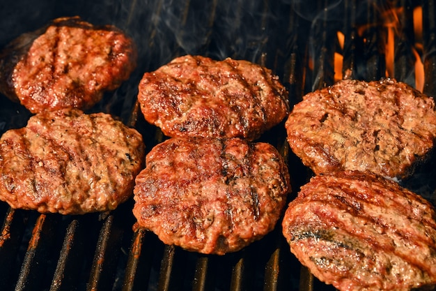 Searing beef meat barbecue burgers for hamburger on bbq fire flame grill with cast iron metal grate