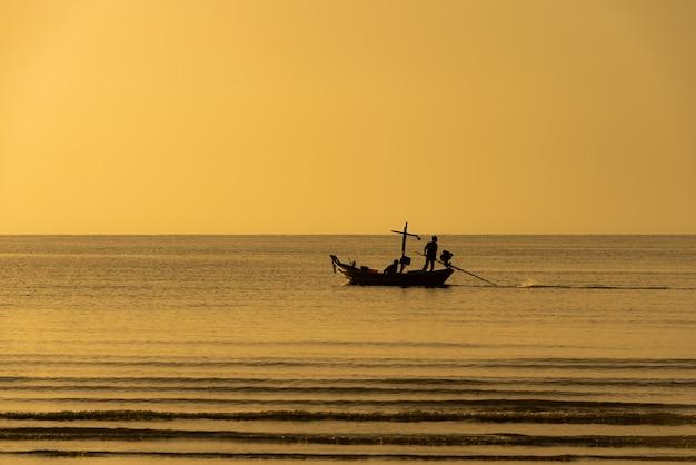 바다 일몰에 떠 있는 작은 어선에 사람들의 바다와 실루엣 이미지가 있습니다