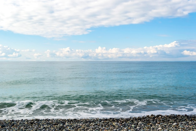 海景:小石と青い曇り空のあるビーチコースト