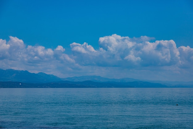 Seascape clouds on the background of mountains and blue sea.
