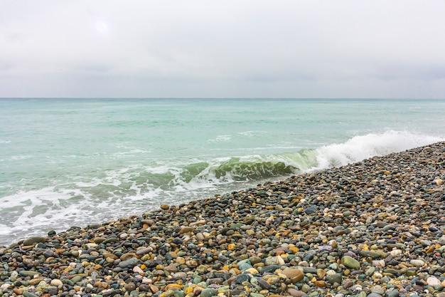 Морской пейзаж в пасмурную непогоду с галькой на пляже