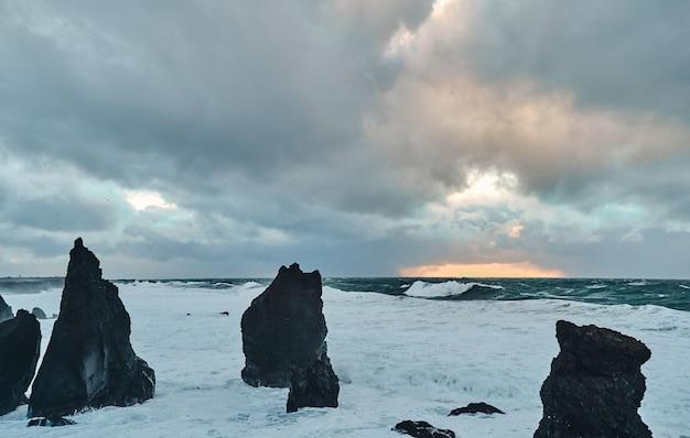 寒い風の強い天候の海景、空は曇り、波は沿岸の黒い石の崖にぶつかります。