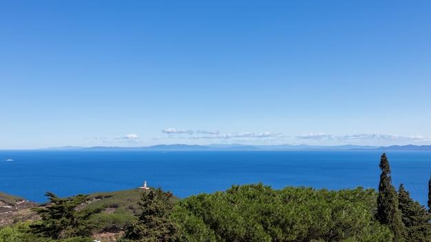 Морской пейзаж острова джильо с маяком на переднем плане и береговой линией тосканы на горизонте