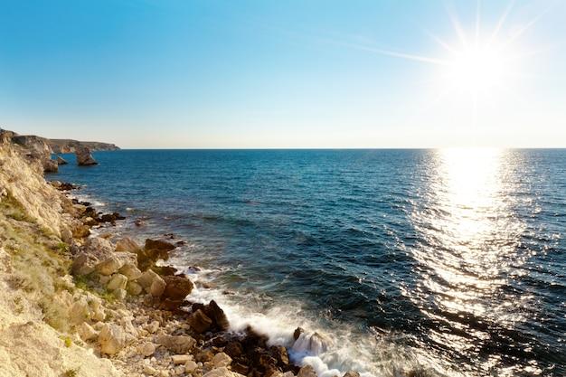 Морской пейзаж берега все еще синего моря, скалистой береговой линии и яркого солнца над водным горизонтом в летний ясный день с голубым небом. неподвижные пейзажи путешествий и мест назначения