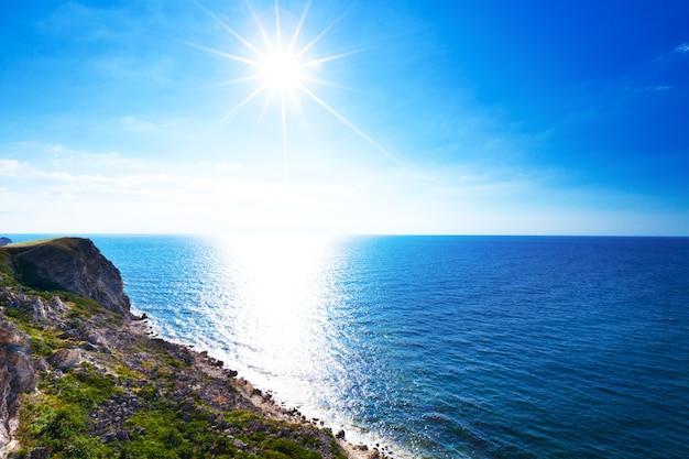 Морской пейзаж берега спокойной голубой морской воды, скалистой береговой линии и яркого солнца