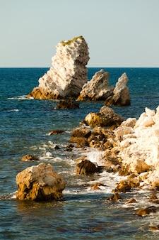 まだ青い海の海の海岸、岩の多い海岸線、明るい太陽の海