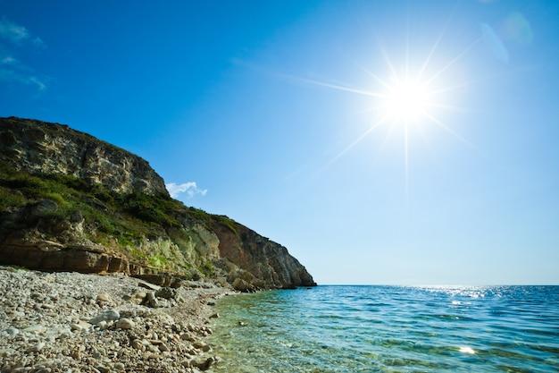 Морской пейзаж берега все еще синей морской воды, каменного пляжа и зеленой скалы