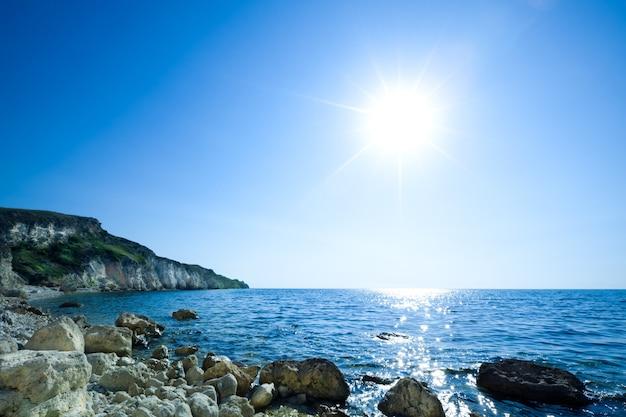 여전히 푸른 바다 해안, 돌 해변 및 녹색 바위의 바다 경치