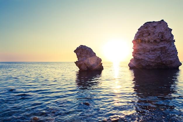 Морской пейзаж спокойного моря, берега, скалистого побережья и романтического розового заката в летний ясный день