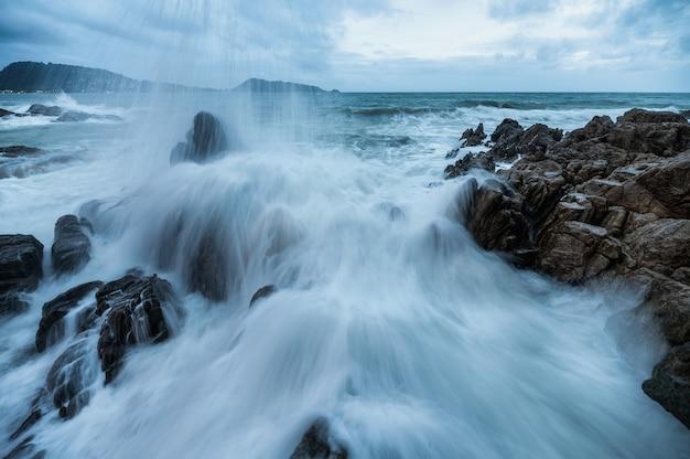 Seascape of powerful big wave hitting and splashing on the rock of coastline in overcast day at phuket