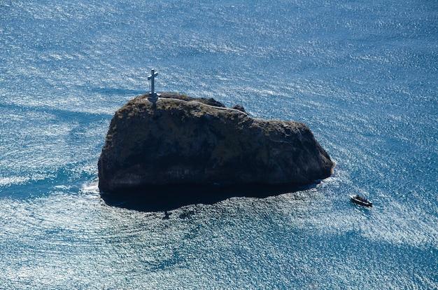 シースケープ。上部にクロスがあるロックアイランド。岩の背景にプレジャーボート。ボート旅行と冒険。