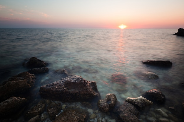 Seascape of still sea waters shore, rocky coastline and romantic pink sunset