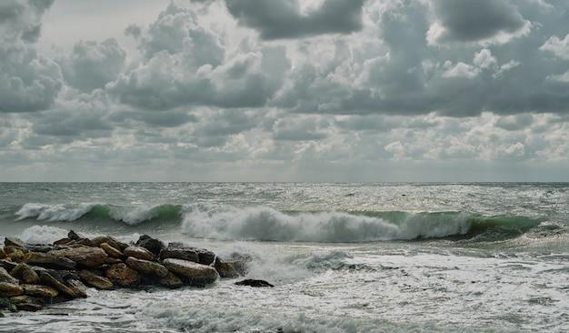 Морской пейзаж, волны разбиваются о каменный волнорез. осенняя буря на побережье, с волнами в белой пене, красивое небо с облаками, солнечный и ветреный день