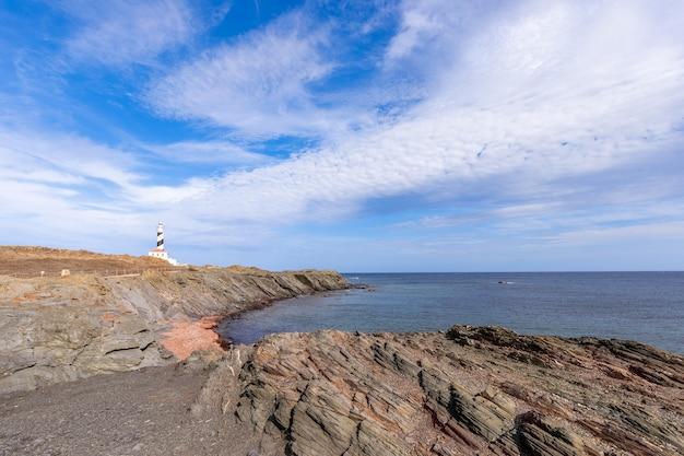 Морской пейзаж с тихой морской бухтой и маяком (faro de favaritx) на острове менорка, балеарские острова, испания