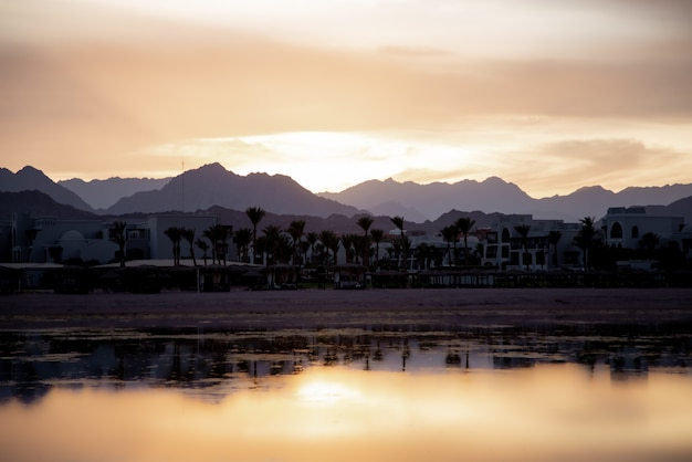反射する空のある海の景色。山の近くの街に太陽が沈む。