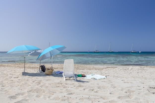 Морской пейзаж с зонтиками и бирюзовым морем на пляже ses salines. остров ибица. балеарские острова, испания