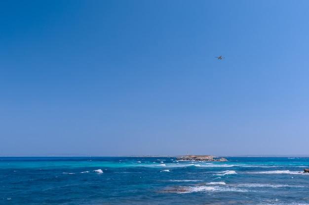 Морской пейзаж с красивым синим морем и. вдали маяк, гидросамолет в воздухе летит к острову форментера. ибица. балеарские острова. испания