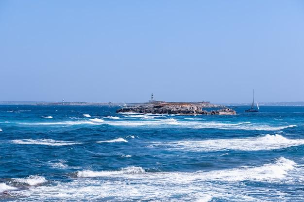 Морской пейзаж с красивым синим морем и маяком у побережья острова форментера. балеарские острова. испания
