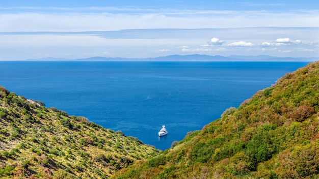 바다에 보트와 바다입니다. 수평선과 삼각형을 이루는 두 개의 언덕을 통해보기