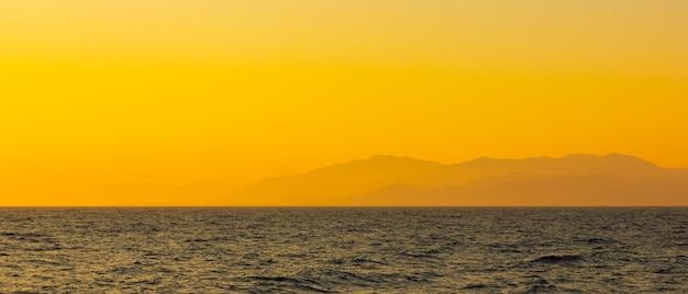 霧と山々の海景。日没時の海景。ドラマチックなシーンと自然の美しさ