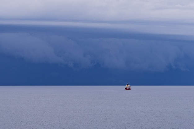 Seascape with large thunderstorm clouds above sea surface with tugboat