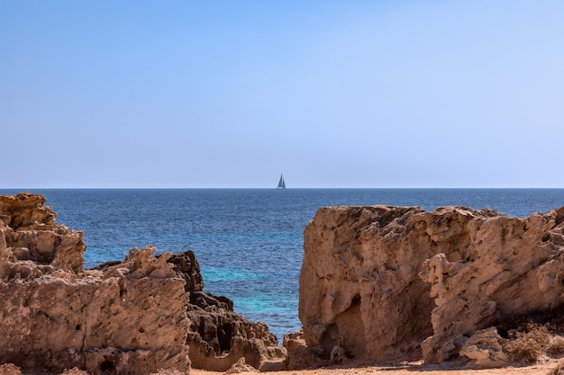 Seascape with lonely sailing yacht at sea and rocky coast of ibiza island
