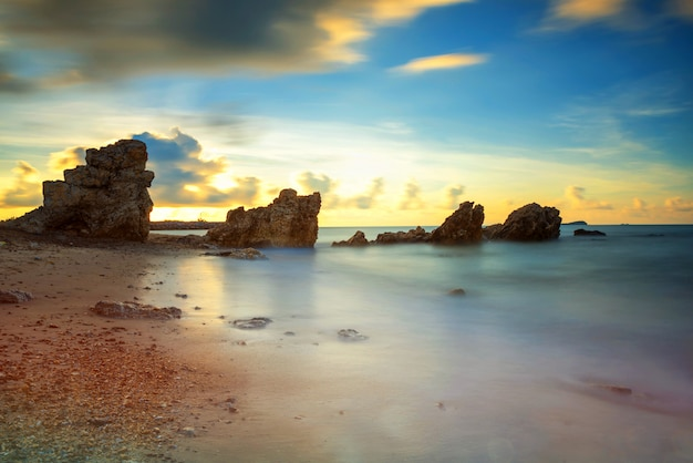 Seascape with natural stone arch at sunrise