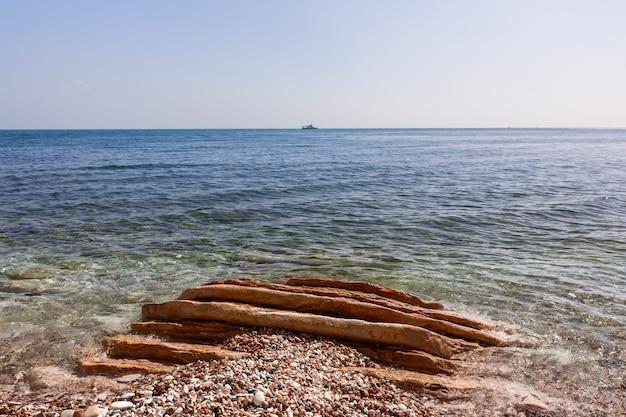 Морской пейзаж с галечным берегом и корабль в море.