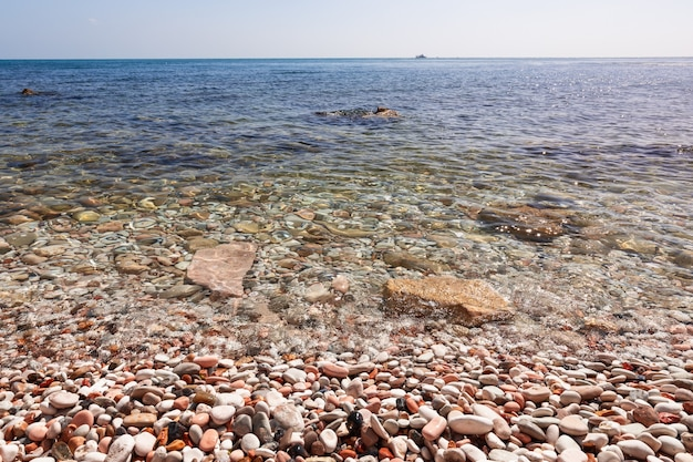 Морской пейзаж с галечным берегом, чистой морской водой и кораблем в море