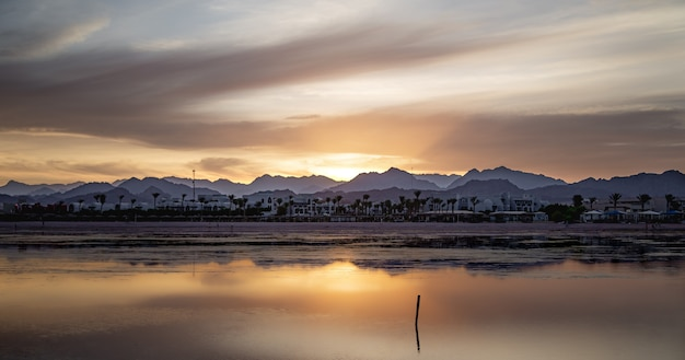 Seascape with a reflecting sky. the sun sets over the city near the mountains.