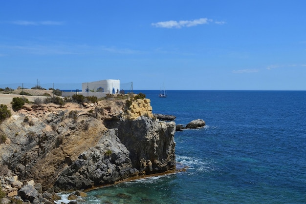 Seascape with rock cliff with building in mediterranean sea.