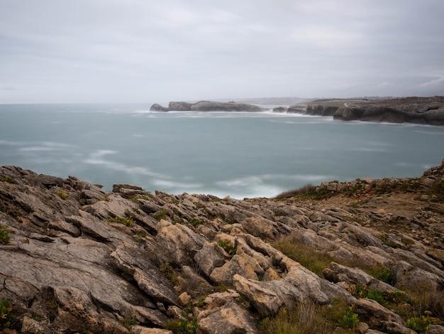 カンタブリアの海岸の曇りの日に岩のある海の景色
