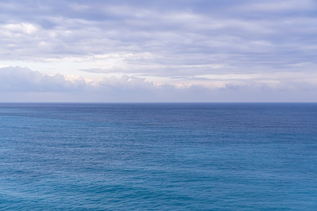 Seascape with sea horizon and almost clear deep blue sky, background, copy space