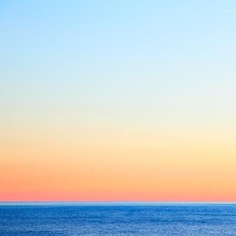 Морской пейзаж с морским горизонтом и красочным ясным небом после захода солнца. фон и место для текста