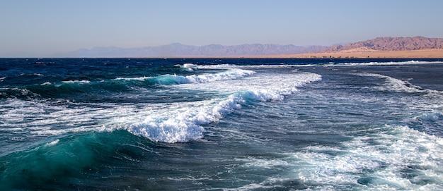 Морской пейзаж с текстурированными волнами и силуэтами гор на горизонте.