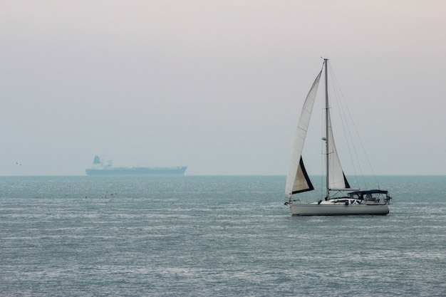 Seascape with a view of a yacht with sails and a cargo ship away on the horizon